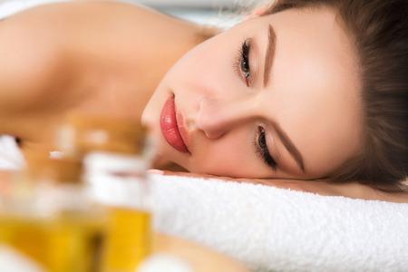 Schöne junge Frau im Wellness-Salon im Liegen. Haut- und Körperpflege, gesunde Lebensweise, Entspannung, Massage und Kosmetik-Konzept Standard-Bild