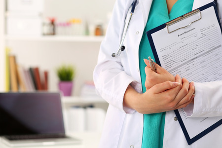 Close up view of female doctor hands holding clipping pad with patient registration form. Healthcare and medical service concept. Stock Photo