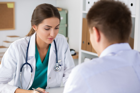 Female doctor writing prescription to her male patient or conculting to her colleague. Physical exam, er, disease prevention, ward round, visit check, 911, prescribe remedy, healthy lifestyle concept photo