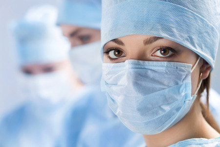 md: Close up portrait of young female surgeon doctor surrounded by her team. Group of surgeon in operation theatre. Healthcare, medical education, emergency medical service and surgery concept