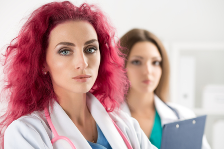 standing reception: Portrait of two doctors standing at reception meeting patients and ready to work. Health care, medical service and teamwork concept.