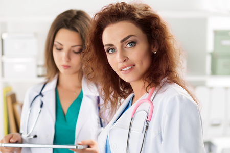 Portrait of two female doctors standing with clipboard and tablet ready to work. Health care, medical service or education and teamwork concept. Stock Photo