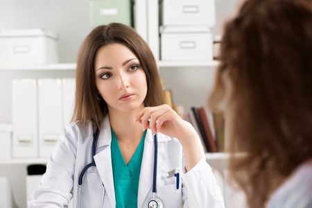 prophylaxis: Young attentive doctor consulting patient. Patient sitting at doctor office. Diagnostic and prevention of women diseases, healthcare and medical service concept