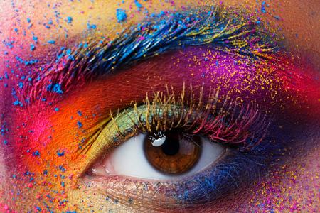 祭り: Close up view of female eye with bright multicolored fashion makeup. Holi indian color festival inspired. Studio macro shot