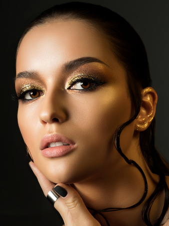 Portrait of young beautiful woman with fashion golden makeup and wet hair. Beauty studio shot. Standard-Bild