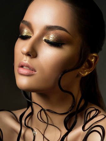 Portrait of young beautiful woman with fashion golden makeup and wet hair. Beauty studio shot. Stock Photo