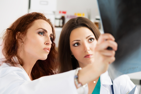 Two female medicine doctors looking at patient lungs x-ray image. Radiology, oncology, healthcare, team work, medical treatment, education or service  concept. Stock Photo