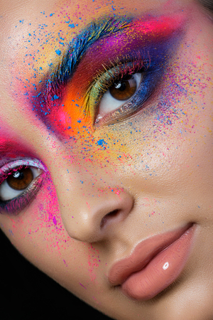 Close up view of female face with bright multicolored fashion makeup. Holi indian color festival inspired. Studio macro shot Stock Photo