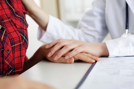 poronienie: Close up view of female doctor touching patient hand for encouragement, empathy, cheering, support after medical examination. Trust and ethics concept. Bad news, healthcare and medical service concept Zdjęcie Seryjne