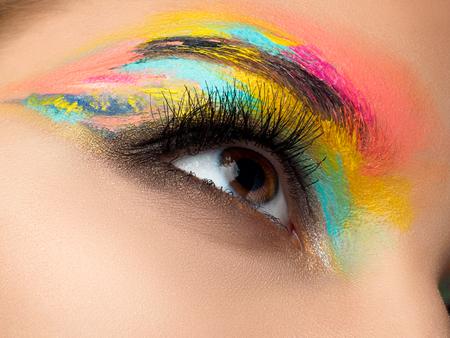 Primo piano di blu donna con gli occhi bella marrone con sfumature rosso e arancio smokey occhi trucco. moda moderna make up.