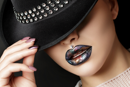 De jonge vrouw met manier maakt omhoog haar ogen verbergend onder zwarte hoed. Mode schoonheid portret. Moderne make-up. Donkere lippen met kleurrijke metallic tinten. Studio opname