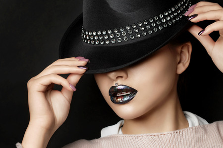 Young woman with fashion make up straightens her hat. Fashion beauty portrait. Modern makeup. Dark lips with colorful metallic tints. Studio shot Stock Photo