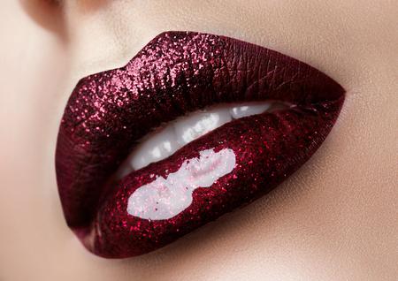 Close up view of beautiful woman lips with dark red lipstick. Fashion make up. Studio shot