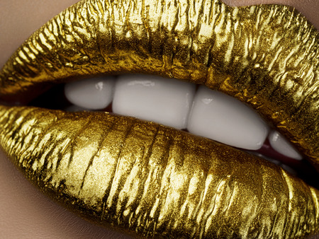 Close up view of beautiful woman lips with golden metallic lipstick. Open mouth with white teeth. Cosmetology, drugstore or fashion makeup concept. Beauty studio shot. Passionate kiss