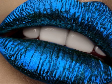 brilliant: Close up view of beautiful woman lips with blue metallic lipstick. Open mouth with white teeth. Cosmetology, drugstore or fashion makeup concept. Beauty studio shot. Passionate kiss