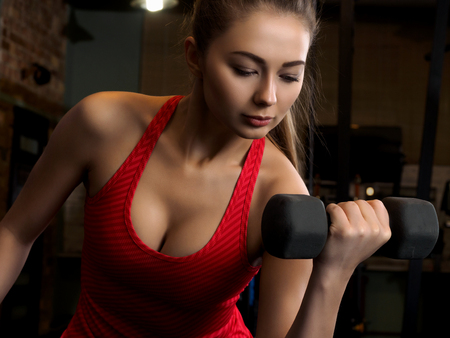 salud y deporte: Woman lifting dumbbells in the gym. Weightlifting in sports club, health care, hobby and leisure activity, health care, healthy life style, slim and fit concept