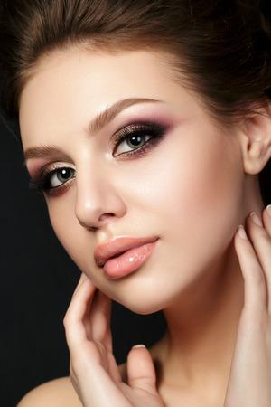 Portrait de la belle jeune femme avec soirée maquillage toucher son visage sur fond noir. yeux smokey multicolores. soins de la peau de luxe et le concept de maquillage de la mode moderne. Studio shot. Banque d'images
