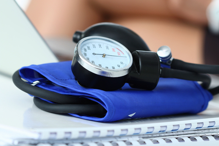 Medicine doctor working place. Close up view of manometer laying on working table at physician office. Hospital workspace. Healthcare, medical service, treatment, hypotonia or hypertension concept. Stock Photo