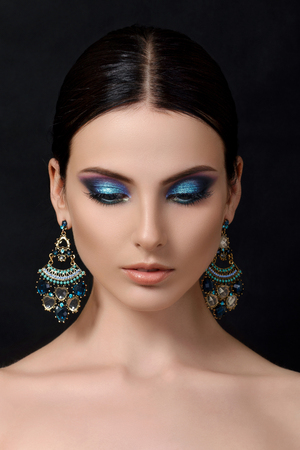 Portrait of beautiful brunet woman with blue earrings posing over black background. Modern fashion make up. Studio shot photo