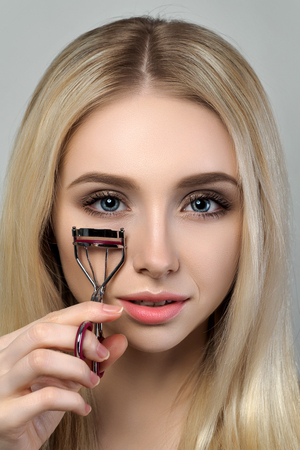 Young beautiful blonde woman looking at the mirror and holding an eyelash curler. Cosmetics, beautician and makeup tips and mistakes concept Stock Photo