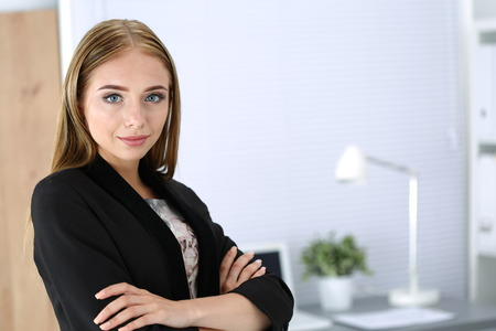 Smiling business woman with folded hands standing at her office. Student or young businesswoman