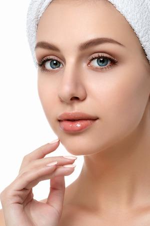 白い背景の上に隔離された彼女の顔に触れる若い美しい白人女性の肖像画。掃除顔、完璧な肌。SPA療法、スキンケア、美容、脱毛または整形手術の