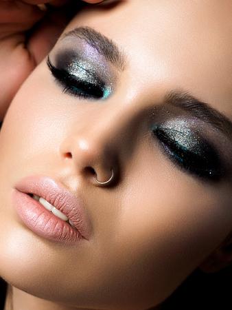 Nahaufnahme der jungen schönen Frau. Perfektes Make-up für Haut und Abend. Silberne rauchige Augen. Makro-Studioaufnahme. Sinnlichkeit, Leidenschaft, Kosmetologie und modernes Make-up-Konzept.