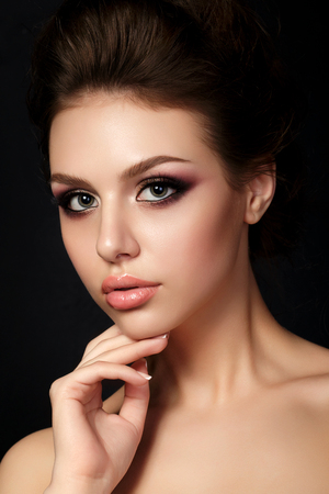 Portrait of young beautiful woman with evening make up touching her face over black background. Red and gold multicolored smokey eyes. Luxury skincare and modern fashion makeup concept. Studio shot.