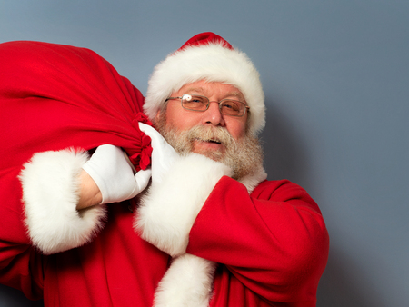 Santa Claus is holding a huge bag of gifts on his shoulder. Christmas miracle, celebration and gifts concept.