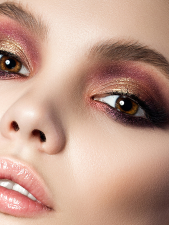 Beauty portrait of young woman with modern smokey eyes. Perfect skin and fashion makeup. Sensuality, trendy luxurious makeup and cosmetology concept. Studio shot.