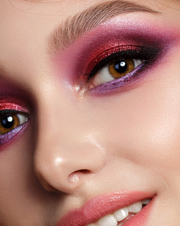 Closeup portrait of young beautiful woman with bright pink smokey eyes and lips. Fashion makeup. Studio shot. Modern summer make up