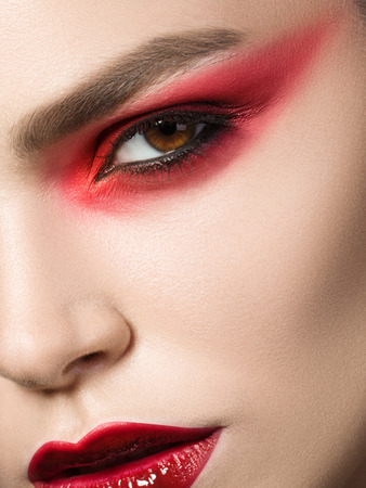 Close up beauty portrait of young woman with red smokey eyes. Perfect skin and fashion makeup. Studio shot. Sensuality, passion, trendy youth makeup concept. Stockfoto