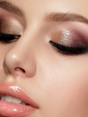 Closeup portrait of young beautiful woman with evening make up. Pink and gold multicolored smokey eyes. Luxury skincare and modern fashion makeup concept. Studio shot. Extreme closeup, partial face view Stockfoto