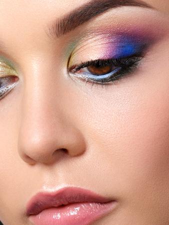 Portrait of beautiful woman with fashion makeup wearing blue earrings. Modern fashion makeup. Multicolor smokey eyes. Studio shot. Extreme closeup, partial face view Stockfoto