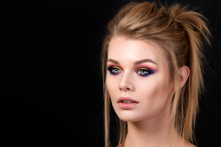 Portrait of young beautiful woman with evening make up posing over black background. Red and gold multicolored smokey eyes. Luxury skincare and modern fashion makeup concept. Studio shot.