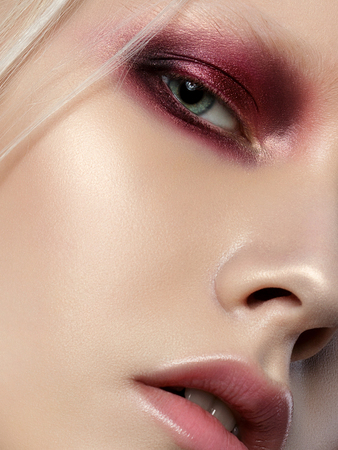 Beauty portrait of young woman with white brows and hair. Perfect skin and fashion makeup. Red smokey eyes. Studio shot. Sensuality, passion, trendy youth makeup concept. Extreme closeup, partial face view Stockfoto