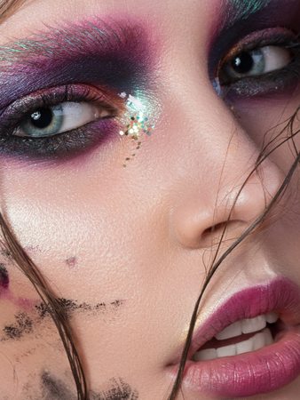 Beauty portrait of a young girl with fashion creative make-up. Colorful smoky eyes. Studio shot. Sensuality, passion, trendy youth makeup concept. Extreme closeup, partial face view