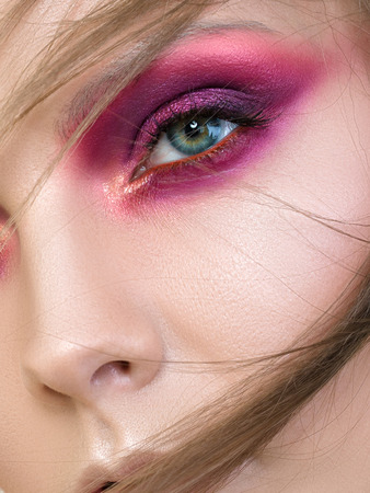 Close up beauty portrait of young woman with purple smokey eyes. Perfect skin and fashion makeup. Studio shot. Sensuality, passion, trendy youth makeup concept. Extreme closeup, partial face view Imagens