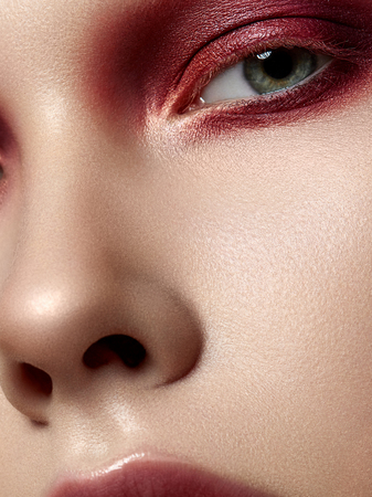 Close up beauty portrait of young woman with white brows and red smokey eyes. Perfect skin and fashion makeup. Studio shot. Extreme closeup, partial face view