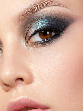 Close up beauty portrait of young woman with beautiful fashion makeup. Modern fashion makeup. Colorful smokey eyes. Studio shot. Extreme closeup, partial face view