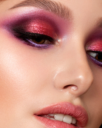 Closeup portrait of young beautiful woman with bright pink smokey eyes and lips. Fashion makeup. Studio shot. Modern summer make up. Extreme closeup, partial face view Stockfoto