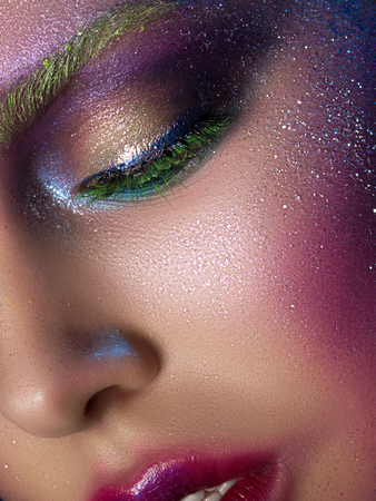 Portrait of young beautiful woman with modern fashion creative makeup. Catwalk or halloween make up. Studio shot. Extreme closeup, partial face view