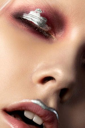 Close up beauty portrait of young woman with red and silver make up. Perfect skin and fashion makeup. Studio shot. Sensuality, passion, trendy youth makeup concept. Extreme closeup, partial face view