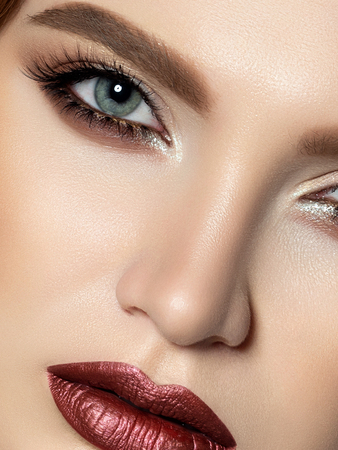 Close up beauty portrait of young woman with dark red lips and brown smokey eyes makeup. Perfect skin and beautiful makeup. Studio shot. Extreme closeup, partial face view Stockfoto