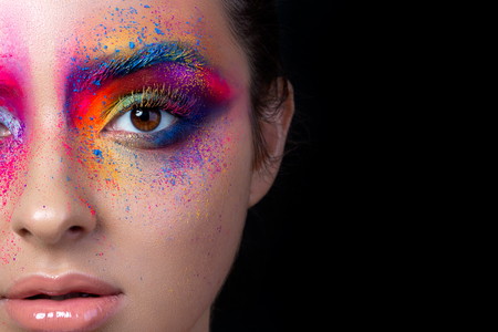 Close up view of female face with bright multicolored fashion makeup. Holi indian color festival inspired. Studio macro shot. Copy space. Stockfoto
