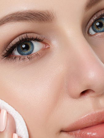 Portrait of young beautiful woman cleaning makeup from her face with cosmetic pad. Cleaning face, perfect skin, skincare and cosmetology concept. Extreme closeup, partial face view