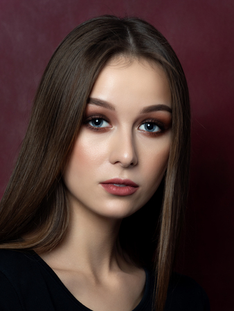 Portrait of young beautiful woman over dark wine red background. Studio shot