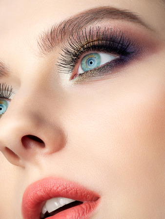 Close up beauty portrait of young woman with beautiful fashion makeup. Modern fashion makeup. Long lashes, colorful smokey eyes. Studio shot. Extreme closeup, partial face view