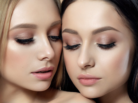 Closeup portrait of two young beautiful women. Creamy beige colors. Nude makeup. Skin care, cosmetics, SPA therapy or cosmetology concept