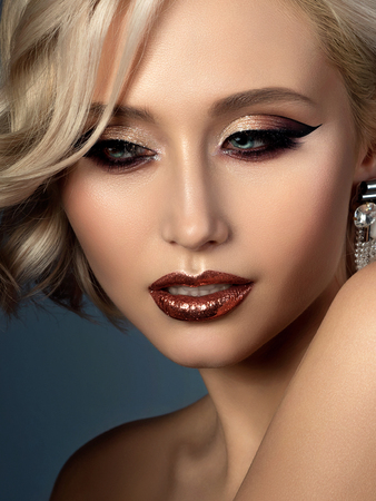 Portrait of young beautiful woman with evening make up. Modern fashion eyeliner wing and glitter on her lips. Studio shot. 写真素材